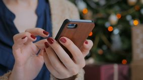Young pretty woman using smartphone at home. Close-up shot of woman hands with smartphone at home. Close up shot. Christmas holiday bokeh background. Technology stock video footage