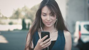 Portrait of young pretty woman using smartphone and listening to music on headphones outdoor at street background. Young pretty woman using smartphone and stock footage
