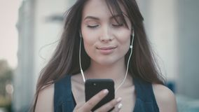 Portrait of young pretty woman using smartphone and listening to music on headphones outdoor at street background. Young pretty woman using smartphone and stock video