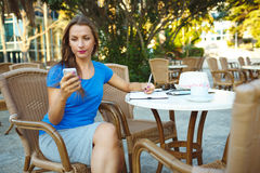 Young pretty woman using smartphone and makes notes in a noteboo Royalty Free Stock Photography