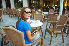 Young pretty woman using smartphone and makes notes in a noteboo Royalty Free Stock Image