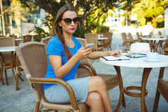 Young pretty woman using smartphone and makes notes in a noteboo Stock Image