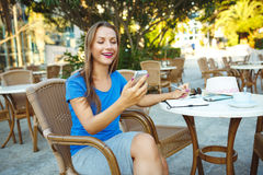 Young pretty woman using smartphone and makes notes in a noteboo Stock Photo
