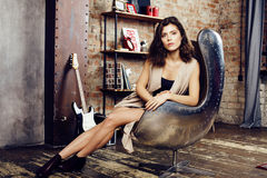 Young pretty woman waiting alone in modern loft studio, fashion musician concept, lifestyle people Royalty Free Stock Images