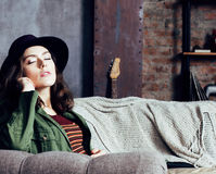 Young pretty woman waiting alone in modern loft studio, hipster in hat, fashion musician concept, lifestyle people Stock Photography