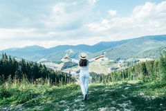 Young pretty woman walking by mountain peak. Young pretty woman in hat walking by mountain peak Stock Photo