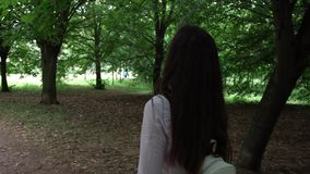 Young pretty woman wanders between trees on green park path. Young pretty woman with long loose hair and white handbag wanders in trees shadow on green park path stock video footage
