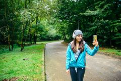 Young pretty woman was interrupted video call while run in the park royalty free stock image