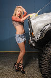 Young pretty woman washes off-road car Stock Photo