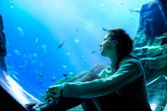 Young pretty woman watching fishes in a tropical aquarium. Young pretty caucasian woman with long curly brunette hair in green sweater watching fishes in a stock image