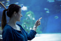 Young pretty woman watching fishes in a tropical aquarium Royalty Free Stock Photography