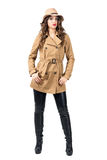 Young pretty woman wearing beige coat and hat posing with hands in pockets. Royalty Free Stock Photos