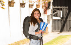 Young pretty woman wearing casual clothing and backpack standing in front of camera, smiling happily, holding travel Stock Image