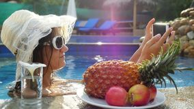 Young pretty woman wears sunglasses and hat takes selfie with mobile phone in swimming pool next to the glasses of the. Water and plate with tropical fruits stock footage