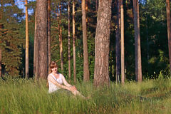 Young pretty woman in white smiles and sits in green grass Royalty Free Stock Image