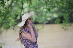 Young and pretty woman who is calling with her smartphone royalty free stock photography