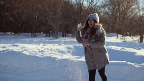 Young pretty woman in winter forest playing snowballs. stock video footage