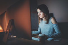 Young pretty woman working on modern studio office at night. Girl using contemporary desktop computer, blurred Stock Photo