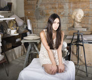 Young pretty woman at workshop in painter studio. Posing like muse, cute brunette girl Royalty Free Stock Photos