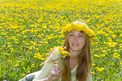 Young pretty woman in wreath of dandelions Royalty Free Stock Photos