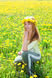Young pretty woman in wreath of dandelions in the Royalty Free Stock Photo