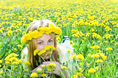 Young pretty woman in wreath of dandelions in the Royalty Free Stock Photos