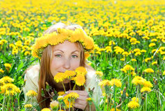 Young pretty woman in wreath of dandelions Stock Photo