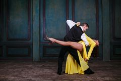 Young pretty woman in yellow dress and man dance tango Royalty Free Stock Photography
