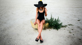 Young pretty women on the beach in black hat Stock Photography