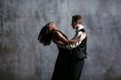 Young pretty woman in black dress and man dance tango. Young pretty women in black dress and men dance tango, training class studio Royalty Free Stock Photo