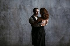 Young pretty woman in black dress and man dance tango. Young pretty women in black dress and men dance tango, training class studio Stock Images