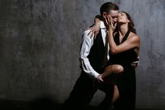 Young pretty woman in black dress and man dance tango. Young pretty women in black dress and men dance tango, training class studio Stock Photos