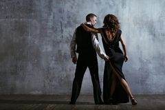 Young pretty woman in black dress and man dance tango. Young pretty women in black dress and men dance tango, training class studio Stock Image
