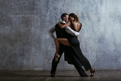 Young pretty woman in black dress and man dance tango. Young pretty women in black dress and men dance tango, training class Stock Photo