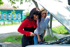 Young pretty women at broken car Stock Images