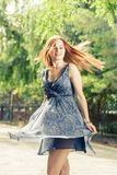 Young pretty women dancing in city park weared blue dress Royalty Free Stock Photography
