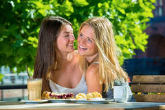 Young pretty women friends in street cafe. Young beautiful women friends sitting close together in street cafe with desserts and coffee, having fun, laughing and Royalty Free Stock Photo