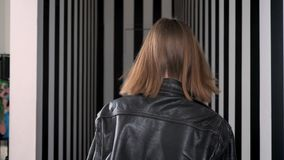 Young pretty women with heavy make up inviting you, walking away and turning around, striped corridor background.  stock footage