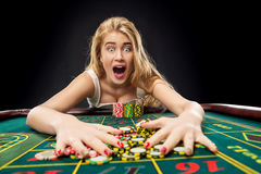 Young pretty women playing roulette wins at the casino. Gambling chips taken by his hands Stock Photos