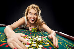Young pretty women playing roulette wins at the casino. Gambling chips taken by his hands Stock Photo