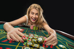 Young pretty women playing roulette wins at the casino. Young pretty woman playing roulette wins at the casino, gambling chips taken by his hands Stock Photo