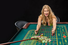 Young pretty women playing roulette wins at the casino. Young pretty woman playing roulette wins at the casino, gambling chips taken by his hands Stock Image