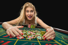 Young pretty women playing roulette wins at the casino. Young pretty woman playing roulette wins at the casino, gambling chips taken by his hands Royalty Free Stock Images