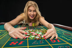 Young pretty women playing roulette wins at the casino. Young pretty woman playing roulette wins at the casino, gambling chips taken by his hands Stock Photography
