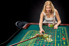 Young pretty women playing roulette wins at the casino. Young pretty woman playing roulette wins at the casino, gambling chips taken by his hands Stock Images
