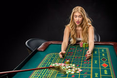 Young pretty women playing roulette wins at the casino. Young pretty woman playing roulette wins at the casino, gambling chips taken by his hands Royalty Free Stock Photography