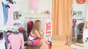 Young pretty women showing her friend a dress stock footage