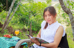 Young pretty young asian woman reading book in the park Royalty Free Stock Photography