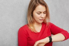 Young pretty young woman checks time on wrist watch, being in hurry or late for meeting, waits for someone, tired of waiting, isol Stock Image