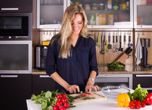 Young pretty young woman cooking salad in kitchen Stock Photos